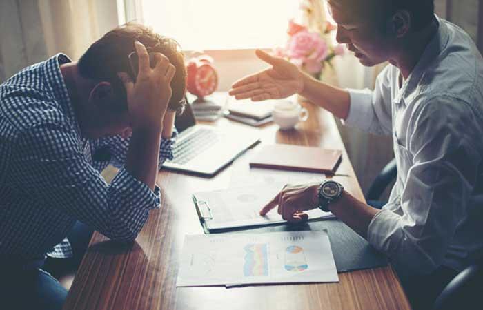 Dos hombres sentados en un escritorio, uno de ellos señala uno de los documentos que está sobre el escritorio mientras el otro hombre se agachaa y agarra la cabeza